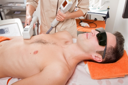cleanse: young man receiving laser epilation on beauty center