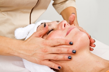 Beautiful young woman receiving facial massage with closed eyes in a beauty center Stock Photo - 23568857