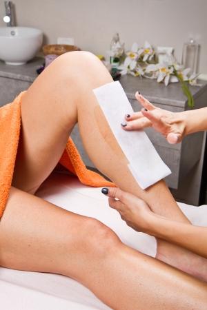 depilacion con cera: Esteticista depilaci�n pierna de una mujer que aplica una tira de material sobre la cera caliente para eliminar los pelos