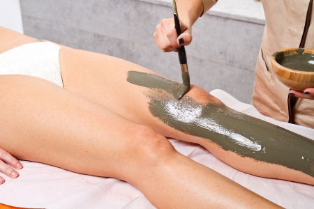 relaxing woman lying on a massage table receiving a mud treatment  Stock Photo - 23568865