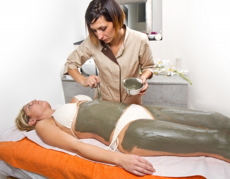 mud woman: relaxing woman lying on a massage table receiving a mud treatment  Stock Photo