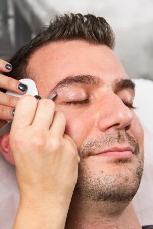 pinzas: Esteticista depilarse las cejas un hermoso hombre con pinzas en un salón de belleza