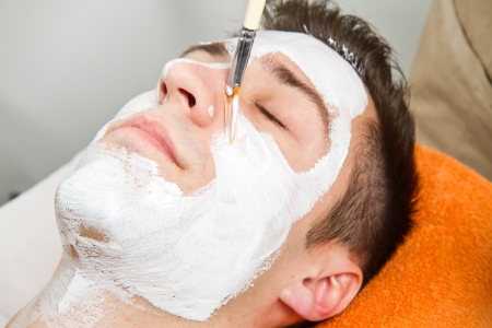 facial treatment: Therapist applying a face mask to a beautiful young man in a spa using a cosmetics brush