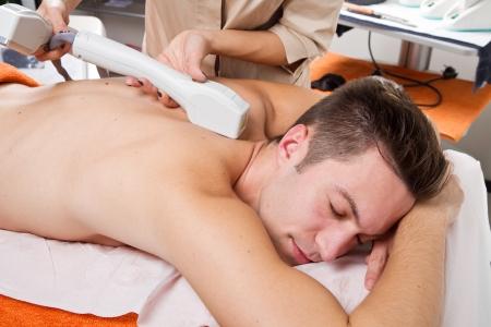waxen: jonge man ontvangen laser epilatie op beautycentrum Stockfoto