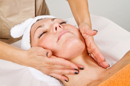 Beautiful young woman receiving facial massage with closed eyes in a beauty center Stock Photo - 23568916