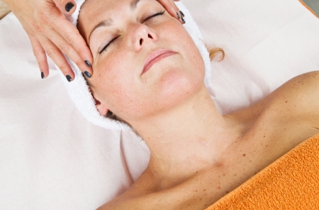 Beautiful young woman receiving facial massage with closed eyes in a beauty center Stock Photo - 23568917