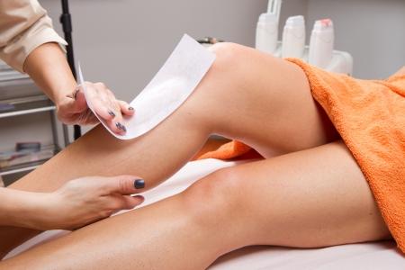 depilacion con cera: Beautician que encera la pierna de una mujer que aplica una tira de material sobre la cera caliente para eliminar los pelos
