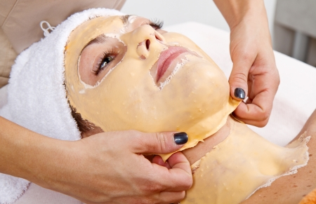 beauty center: Beautiful young woman remove  facial mask  in a beauty center Stock Photo
