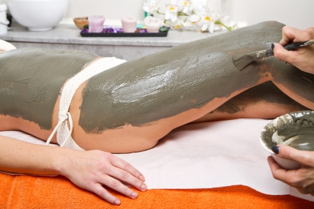 relaxing woman lying on a massage table receiving a mud treatment  Standard-Bild