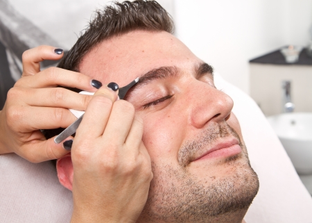 tweezing eyebrow: Beautician plucking a beautiful man eyebrows with tweezers in a beauty salon