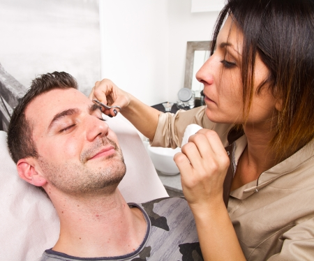 plucking: Beautician plucking a beautiful man eyebrows with tweezers in a beauty salon