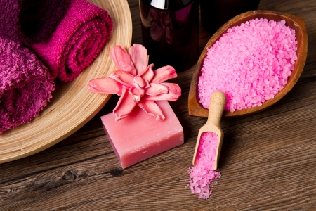pink Spa tools with candle amd towel on wood