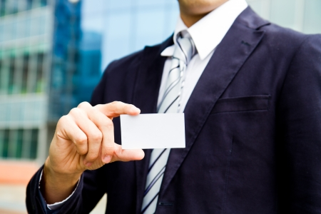 visit card: young businessman holding visit card in hand