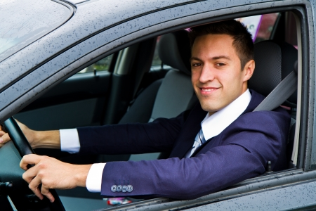new motor vehicle: Portrait of an handsome guy driving his car