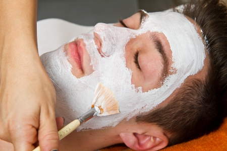 Therapist applying a face mask to a beautiful young man in a spa using a cosmetics brush  photo