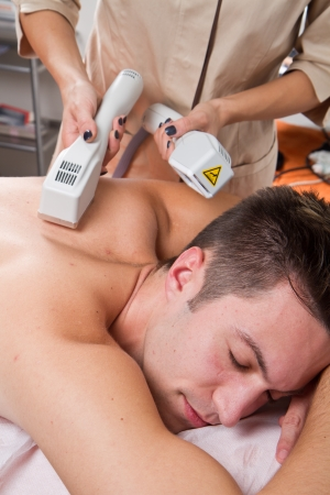 depilacion: hombre joven que recibe la depilación láser en el centro de belleza