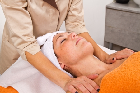 Beautiful young woman receiving facial massage with closed eyes in a beauty center Stock Photo - 24038379