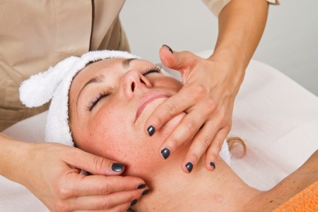 Beautiful young woman receiving facial massage  Stock Photo - 24137518