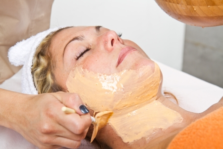 Therapist applying a face mask to a beautiful young woman in a spa using a cosmetics brush  photo
