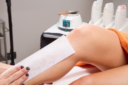 depilaciones: Esteticista depilaci�n pierna de una mujer que aplica una tira de material sobre la cera caliente para eliminar los pelos