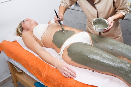 relaxing woman lying on a massage table receiving a mud treatment  photo