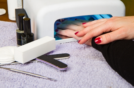 lady with the lamp: Hands with uv lamp for nails  Stock Photo