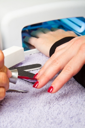 lady with the lamp: manicure and Hands with uv lamp for nails Stock Photo