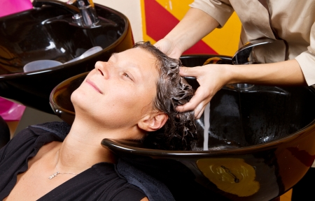 Hairdressers hand washing female customers hair in salon photo