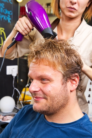 Beautiful man at the hairdresser blow drying his hair photo