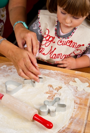 Little girl with mum baking Christmas cookies cutting pastry with a cookie cutter photo