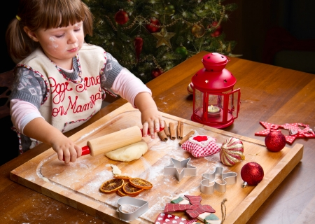 Little girl baking Christmas cookies cutting pastry with a cookie cutter photo