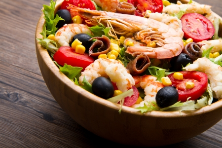 salad greens:  salad of shrimp, mixed greens, black olives anchovies and tomatoes on wooden background