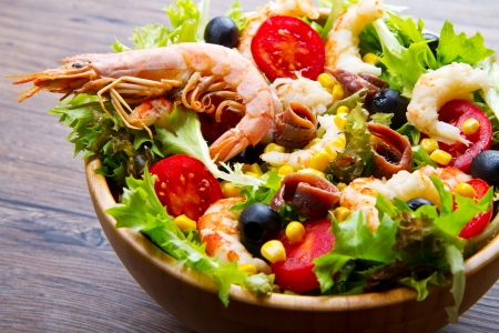 salad of shrimp, mixed greens, black olives anchovies and tomatoes on wooden background photo