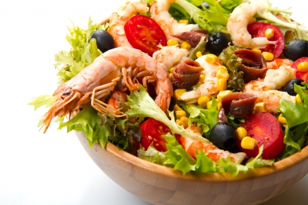 salad of shrimp, mixed greens, black olives anchovies and tomatoes isolated on white photo
