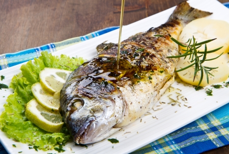 gilt head: Grilled gilt head sea bream on plate with lemon and rosemary and potatoes  Stock Photo