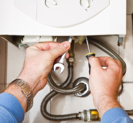 home appliance: Plumber at work. Servicing gas boiler