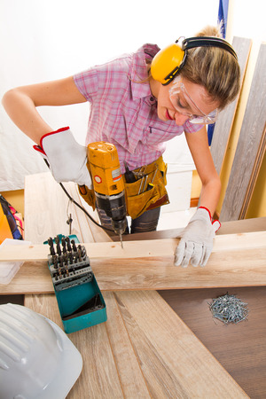 Female carpenter  at work using hand drilling machine photo