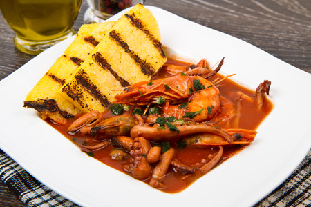 seafood soup: fish soup with grilled polenta on white dish