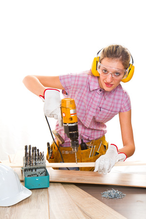 Female carpenter  at work using hand drilling machine photo