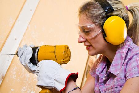 Vrouwelijke timmerman op het werk met handboormachine