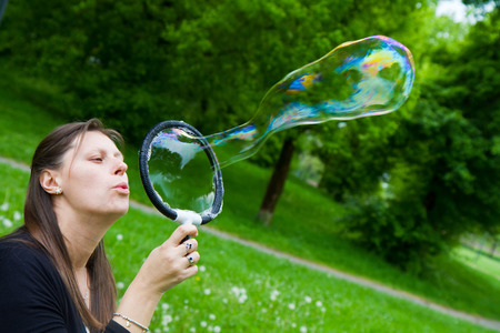 inflating: woman inflating colorful soap bubbles in spring park