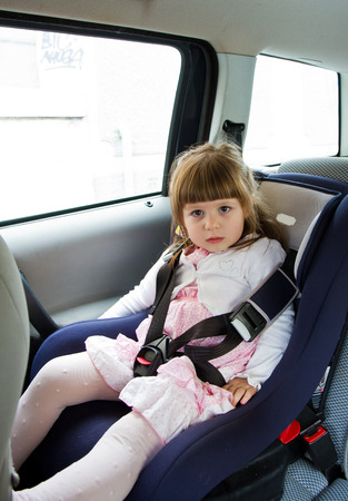 little cute girl sitting in the car in child safety seat and smiling  photo
