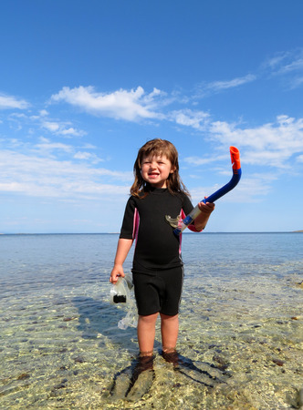 Portrait of happy girl with wetsuit, masks and snorkels at the sea photo