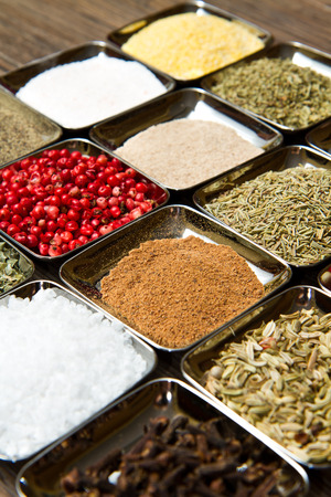 colored and mixed spice in box on wood background photo