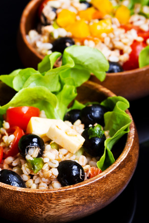 wood bowl with spelt salad with olives and tomatoes photo