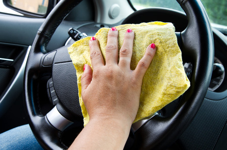microfiber cloth: Womans hand with microfiber cloth polishing wheel of a car