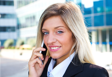 Business woman portrait outdoors talking at the phone photo