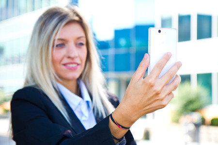 Beautiful business woman takes a selfie with her cell phone photo