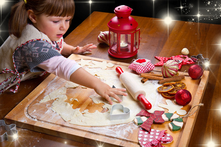 pastry cutter: Little girl baking Christmas cookies cutting pastry with a cookie cutter Stock Photo