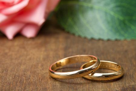 anillos de boda: anillos de bodas con rosas de color rosa sobre fondo de madera